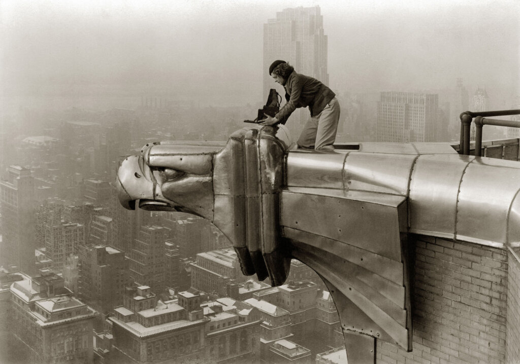 American photographer and journalist Margaret Bourke-White (1904 - 1971) perches on an eagle head gargoyle at the top of the Chrysler Building and focuses a camera, New York, New York, 1935. (Photo by Oscar Graubner/The LIFE Images Collection/Getty Images)