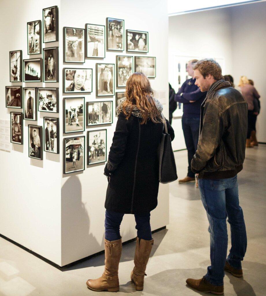 Gli spettatori osservano le fotografie esposte © Fred Ernst