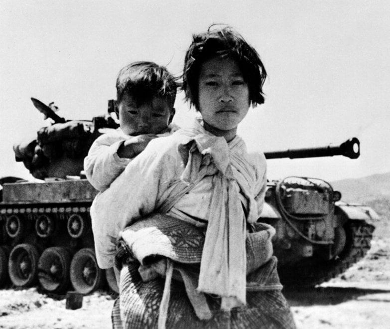 Ragazzina coreana con il fratello sulle spalle durante la guerra di Corea, 1951 © courtesy UN Photo/United States Navy