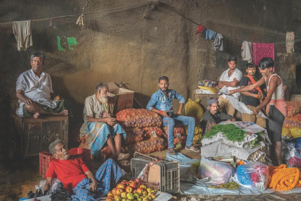 Questa composizione pittorica con un gruppo di uomini in un negozio è una scena tipica delle prime ore del mattino per le strade delle città indiane.