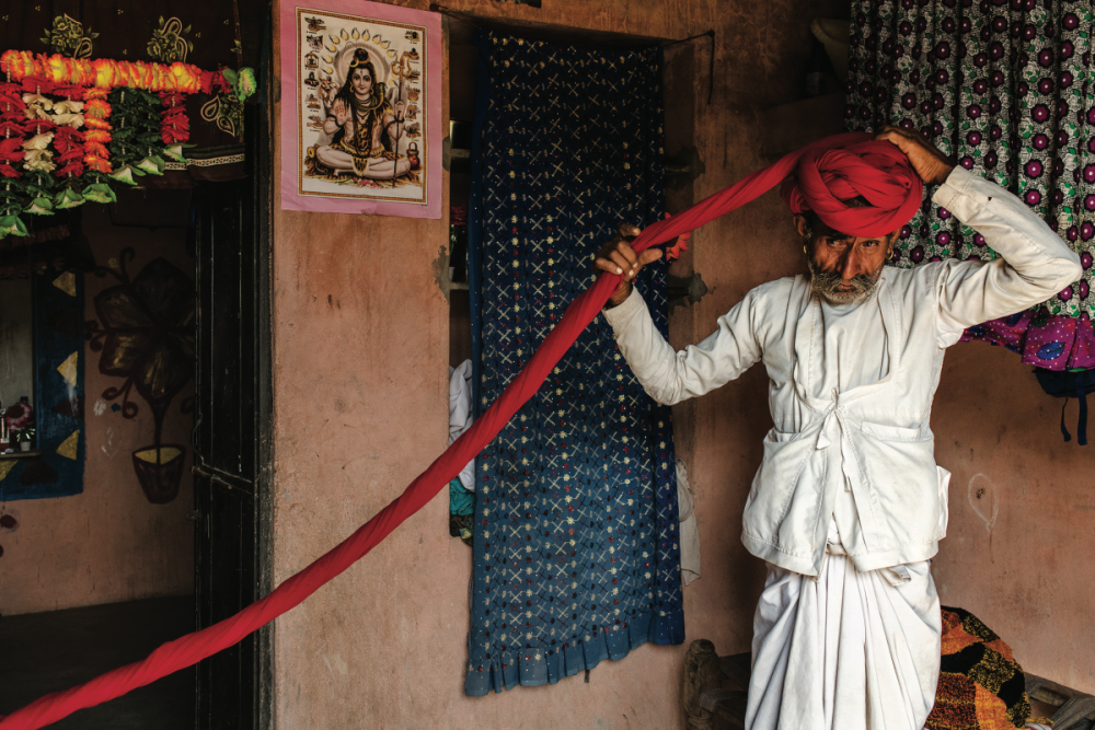 Nella città di Jodhpur, nel Rajasthan, un uomo arrotola con meticolosità il lungo tessuto del turbante che indosserà per il resto della giornata.