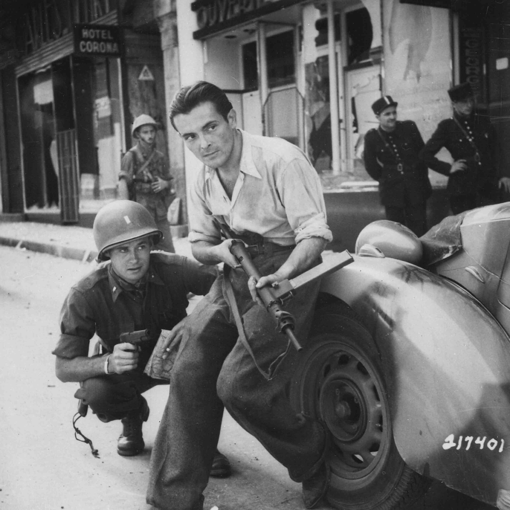 Ufficiale americano e partigiano francese si accovacciano dietro un'auto durante un combattimento in strada in una città Estate, 1944, Francia, autore sconosciuto o non fornito © courtesy U.S. National Archives and Records Administration