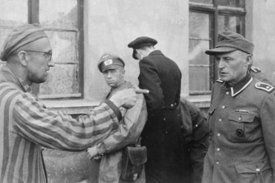 Uno schiavo lavoratore russo liberato dalle forze U.S.A. indica una ex guardia nazista che picchiava brutalmente i prigionieri. 14 maggio 1945, Germania, autore sconosciuto o non fornito © courtesy U.S. National Archives and Records Administration