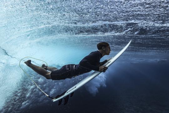 Surfista con tavola sott'acqua