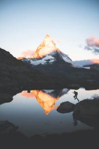 l salto di un alpinista aggiunge dinamismo al primo piano di questa veduta del Cervino e del suo riflesso nel lago alla luce dell'alba.