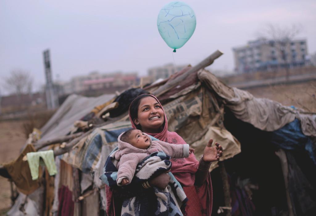 SORRISI, ISLAMABAD, PAKISTAN. Una madre pakistana e sua figlia, sfollate per le inondazioni, giocano con un palloncino fuori dalla loro tenda alla periferia della capitale pakistana.