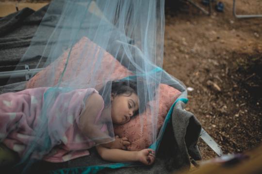 Anna Rahmoni, una rifugiata afghana di 21 mesi dorme all'aperto sotto una rete antizanzare per fuggire dal caldo asfissiante che troverebbe all'interno della tenda della sua famiglia.